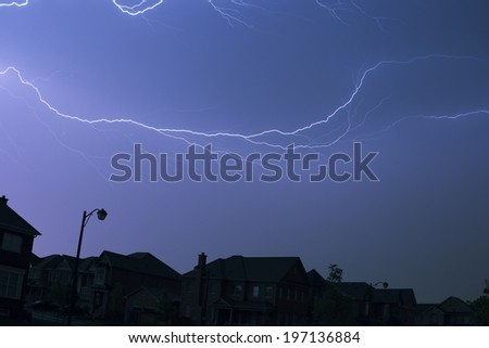 Lightning striking above a neighborhood during the evening. - stock photo