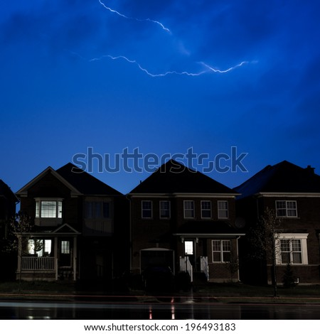 Lightning striking above a row of houses at dusk.