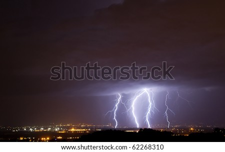 Lightnings over a small town - stock photo