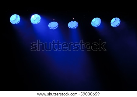 Lights and smoke. Row of blue lights from a stage. - stock photo