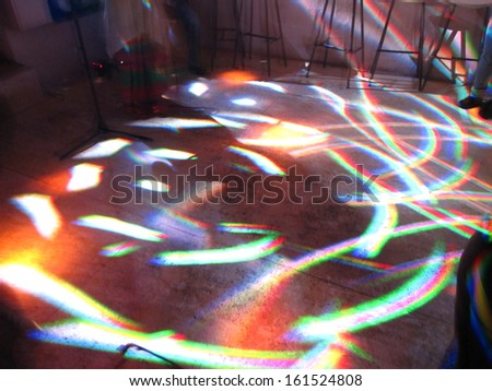 Lights from a light show swirl on the floor. - stock photo