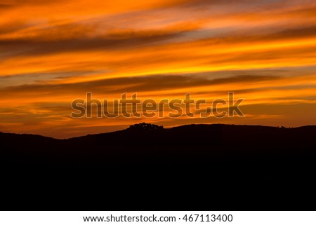 Lights glisten in the hilltop village of Sant' Antonino in Balagne region of Corsica silhouetted against a dramatic orange evening sky