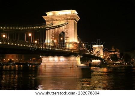 Lights illuminate the large pillars of the Chain bridge at night, Budapest, Hungary - stock photo