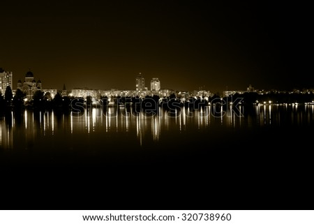 Lights night city with reflections on the river vintage filtered - stock photo