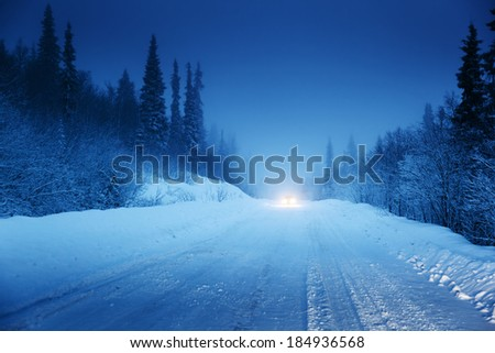 lights of car and winter road in forest - stock photo