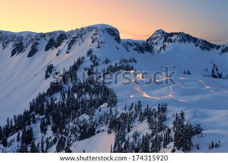 Lights of Snowmobiles on Snow Mountain at Sunset - stock photo