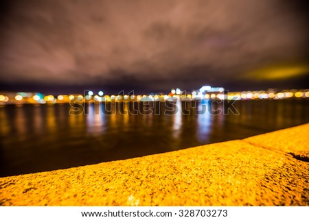 Lights of the city at night, the view from the waterfront. Focus on the border