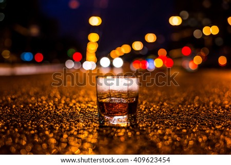 Lights of the city at night through the glass of alcohol, headlights of the approaching car. View from the glass level with brandy standing on the asphalt - stock photo