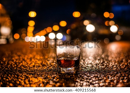 Lights of the city at night through the glass of alcohol, headlights of the approaching cars. View from the glass level with brandy standing on the asphalt - stock photo