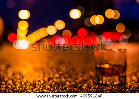 Lights of the city at night through the glass of alcohol, headlights of the approaching cars. View from the glass level with brandy standing on the asphalt, defocused image - stock photo