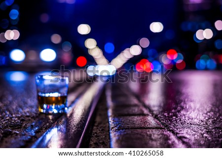Lights of the city at night through the glass of alcohol, night ?venue with rails for trams and driving car. View from the level of the rails on which stands a glass of brandy, in blue tones - stock photo