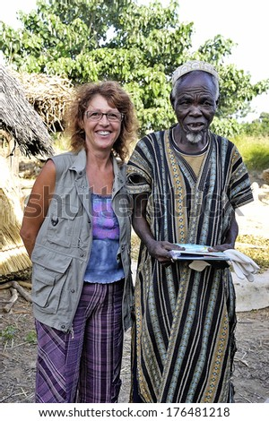 LIGUIDI MANGAM, BURKINA FASO - NOVEMBER 11 : a French tourist makes a visit to a village in Burkina Faso and befriends the village chief, november 11, 2010 - stock photo