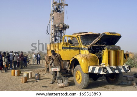 LIGUIDIMALGEM,  BURKINA FASO - FEBRUARY 24: In Africa the water is underground, overall view of the drill and the old truck that supports, February 24, 2007 - stock photo