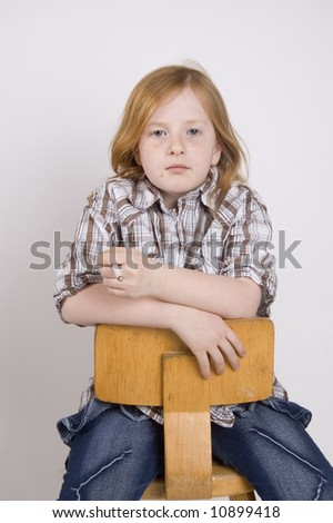liittle girl sitting on a chair smoking a cigarette