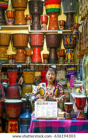 Lijiang, China - April 10,2017 : A chinese girl playing the djembe in the retail which is located at the Old Town of Lijiang in Yunnan Province, China.