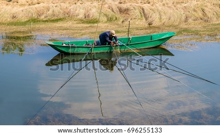 Lijiang,China - April 14,2017 : Lijiang Lashi Lake Wetlands is a national natural scenic spot near the city of Lijiang,China. A person can seen fishing on the lake.