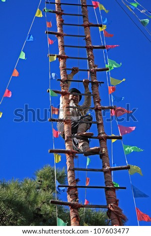 LIJIANG, CHINA - DECEMBER 8, 2010: A barefooted Naxi ethnic man climbs up a ladder made of sharp knives at the Dongba Valley Cultural Village on December 8, 2010 in Lijiang, Yunnan Province of China.