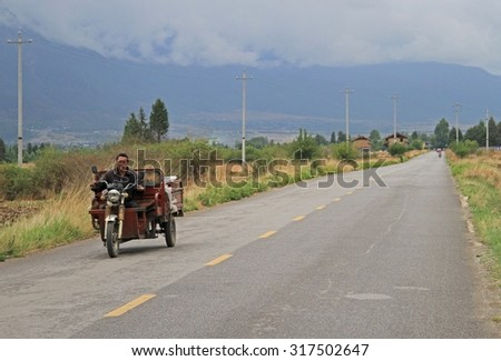 LIJIANG, CHINA - JUNE 11, 2015: man is driving motor tricycle on the road nearly Lijiang, China