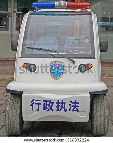 LIJIANG, CHINA - JUNE 10, 2015: police officer is sitting inside police car on the street in Lijiang, China