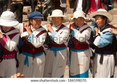 LIJIANG,CHINA-MARCH 17: A group of Naxi nationality old woman dressed in national clothing dancing.Located in Lijiang Dayan Old Town Square street (Sifang Street) on March 17,2014,Yunnan in China.