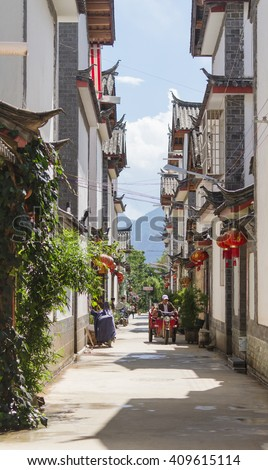 Lijiang, China - Oct 04, 2014: A man drives his electric tricycle through a street amidst Chinese traditional architecture in Shuhe, Lijiang old town in Yunnan province, China