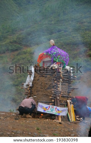 LIJIANG, CHINA - SEPTEMBER 19: Cremation ceremony of Mosuo Minority People, unidentified lama ignites to fire up the coffin, September 19, 2013, Yongning, Linlang, Lijiang, China - stock photo