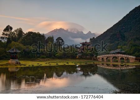 Lijiang old town scene - Black Dragon Pool Park at sunset - stock photo