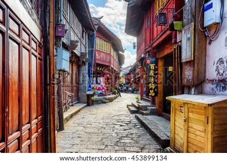 LIJIANG, YUNNAN PROVINCE, CHINA - OCTOBER 23, 2015: Scenic view of narrow street in the Old Town of Lijiang. Beautiful facades of traditional oriental Chinese wooden houses on blue sky background.