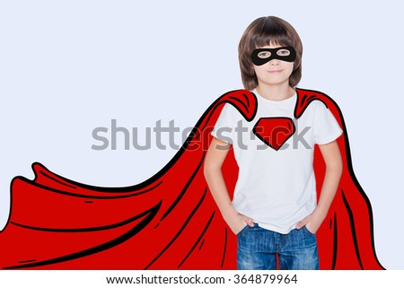 Like a hero. Cheerful boy holding hands in pockets and looking like superhero in his drawn cape while standing against white background - stock photo
