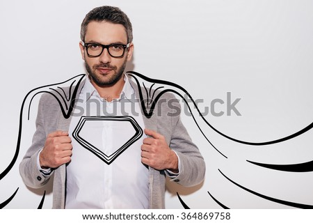 Like a hero. Confident young man adjusting his jacket and looking like superhero in his drawn cape while standing against white background - stock photo