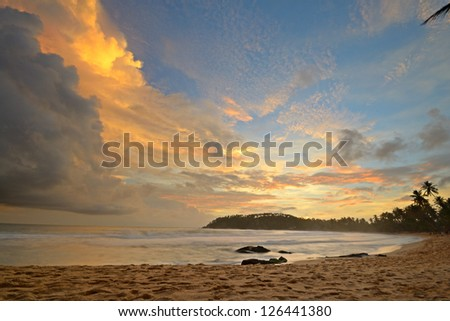Like an atomic explosion, clouds gathering at the horizon at the tropical beach of Mirissa, Sri Lanka. Double exposure shot taken at dusk during monsoon season. - stock photo