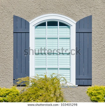Like heritage style design residential window with wooden leafs on the brown wall - stock photo