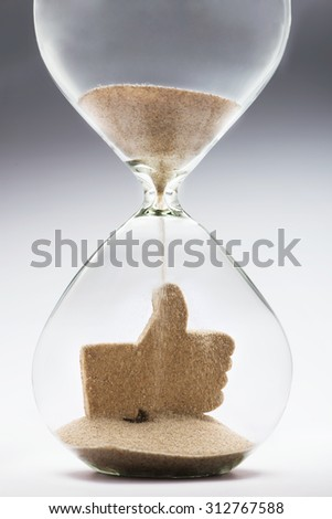 Like icon made out of falling sand inside hourglass - stock photo