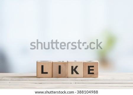 Like message made of cubes on a wooden desk - stock photo
