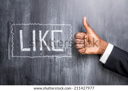 Like this! Close-up of human hand with thumb up in front of the blackboard with inscription Like