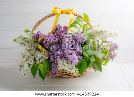Lilac bouquet in basket on background of shabby wooden planks in rustic style