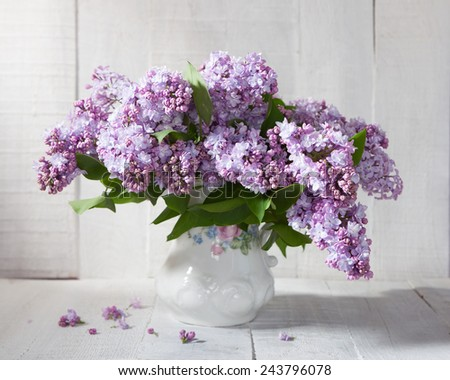 Lilac Bouquet in ceramic jug against a white wooden wall. - stock photo