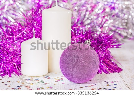 Lilac Christmas ball and two white candles on wooden boards on a blurred background of tinsel. Selective focus - stock photo