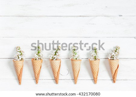 Lilac flowers in ice cream cone. Pattern. Creative flowers. Flat lay, top view - stock photo