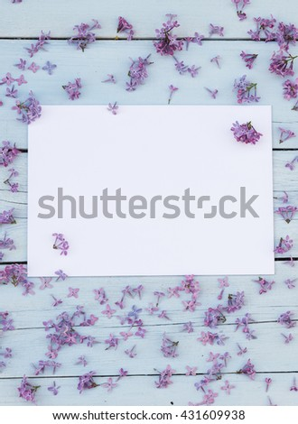 Lilac spring flowers with blank paper for greeting message on a light blue shabby wooden background. Vintage Floral mock up with purple flowers. Copy space - stock photo