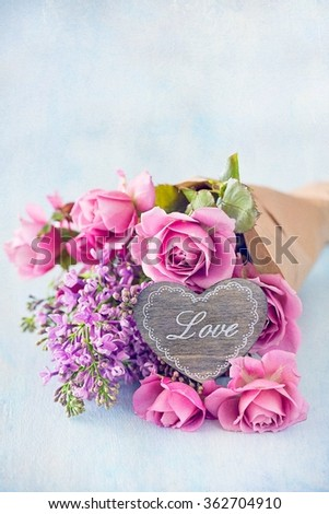 Lilacs and pink roses flowers decorated with a wooden heart. .Floral gift for a wedding or birthday. - stock photo