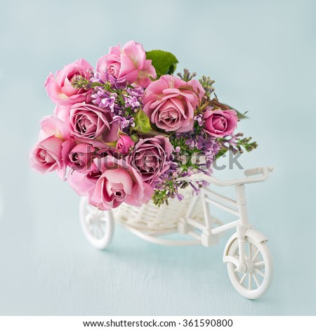 Lilacs and pink roses flowers in a decorative white wooden bicycle on a blue background .Floral gift for a wedding or birthday. - stock photo