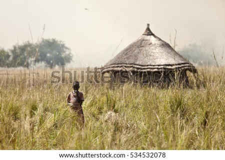 LILIIR, SOUTH SUDAN-DECEMBER 4, 2010: Unidentified child stands in front of a hut with smoke from grassfires in the background