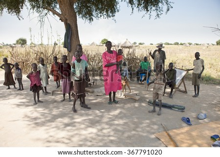 LILIIR, SOUTH SUDAN-DECEMBER 4, 2010: Unidentified large family stands in the shade of a tree in rural South Sudan - stock photo