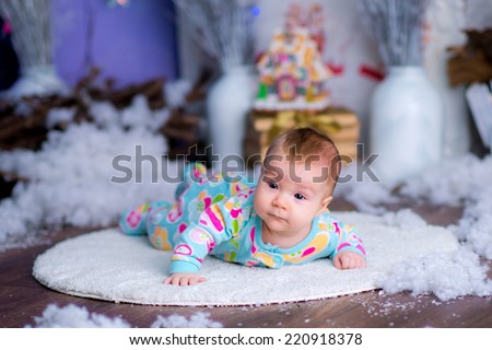 lille cute funny kid in a New Year's suit near a Christmas tree. blue accent decor - stock photo