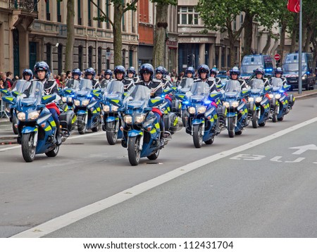 LILLE, FRANCE - JULY 14: A motorcycle unit of the French police riding in formation during a traditional Bastille Day parade through the city of Lille, France on July 14, 2012 - stock photo