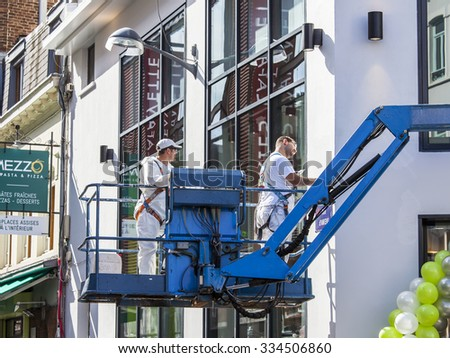 LILLE, FRANCE, on AUGUST 28, 2015. Typical city street in the bright sunny day. Workers wash windows