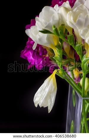 Lily flower bouquet in vase on black background shot sideways - stock photo