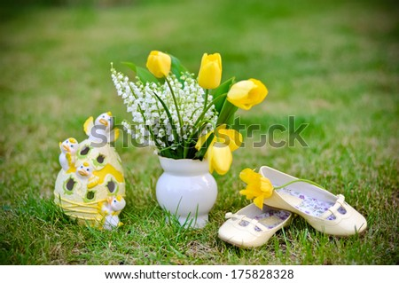 Lily of the valley and yellow tulips in flowerpot with Easter decorations and child's shoes isolated on the lawn - stock photo