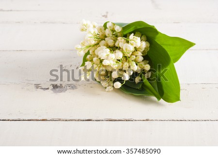 lily of the valley flowers on bright wood table  - stock photo